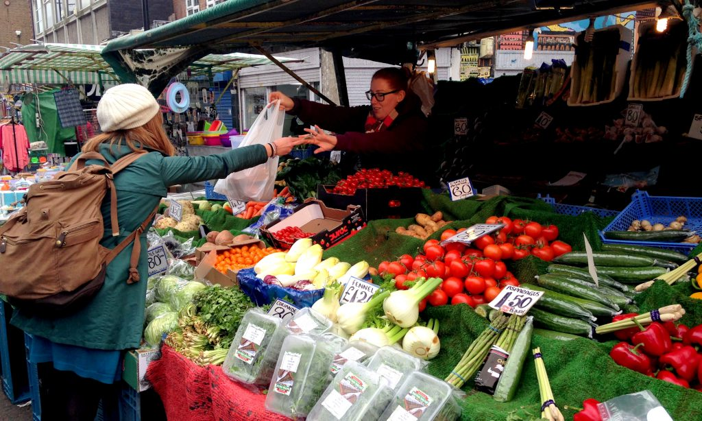 A woman buys fresh vegetables at London Farmers' Market